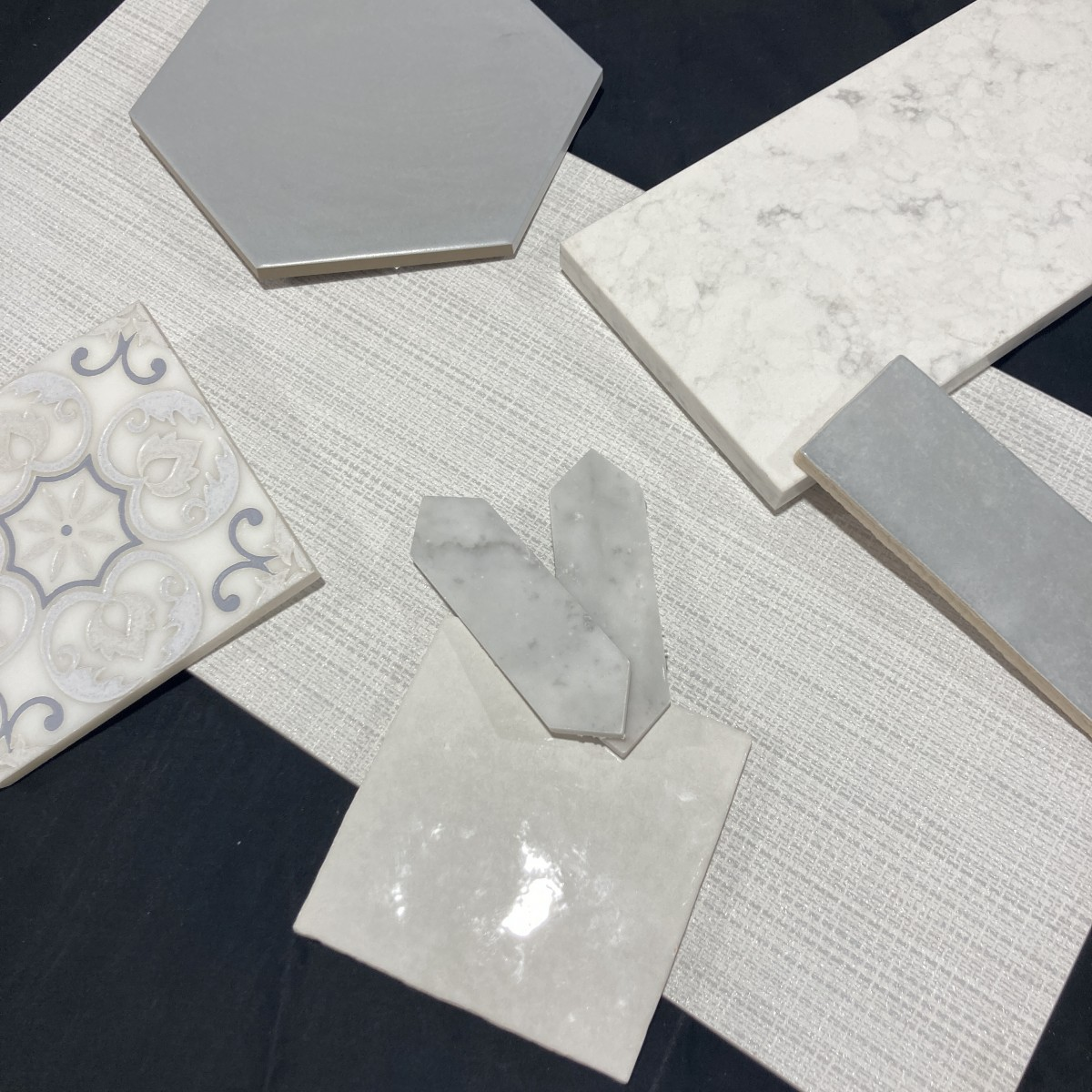 A mix of white and gray ceramic, porcelain, and glass tiles.