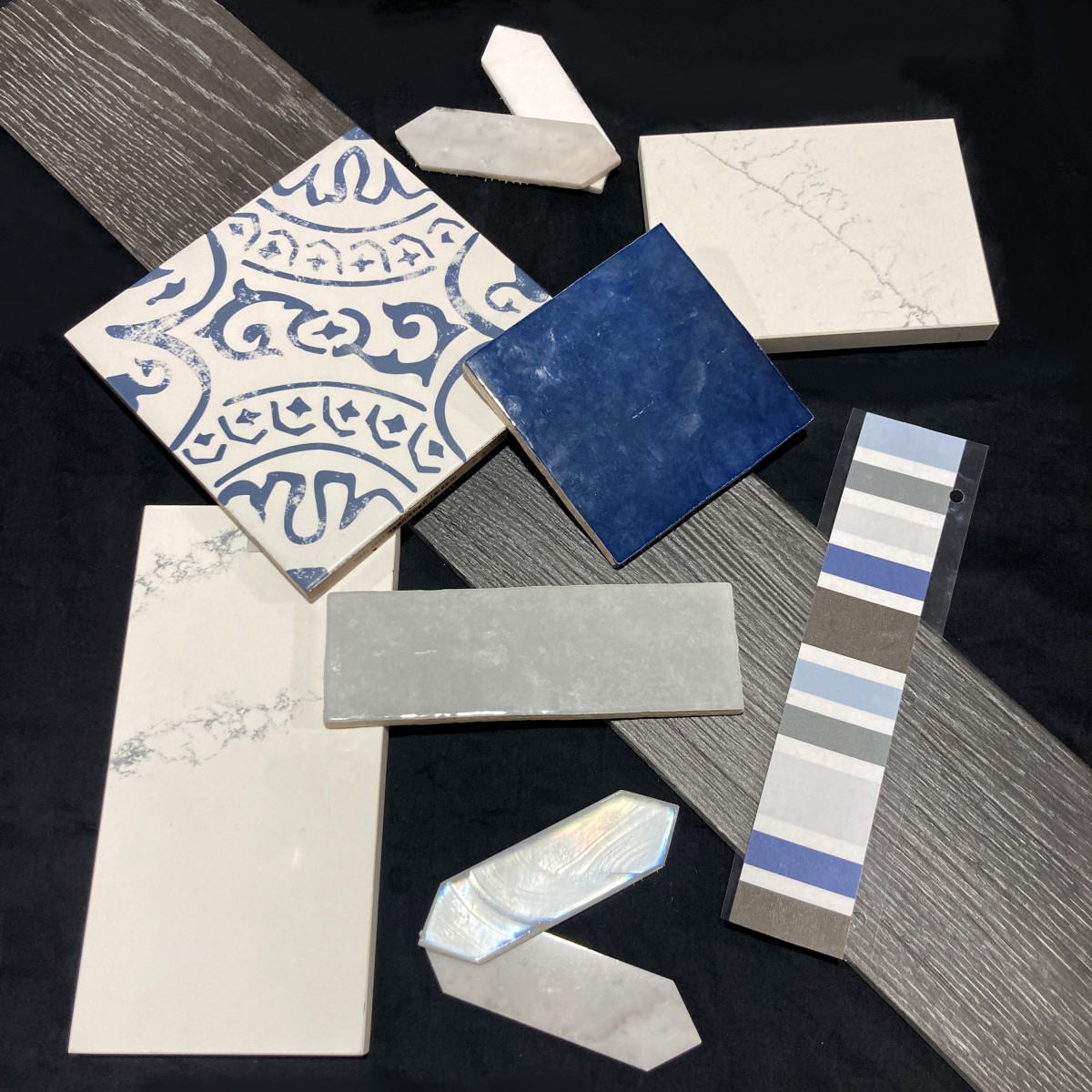 A mix of blue, gray, and white porcelain, ceramic, and glass tiles.