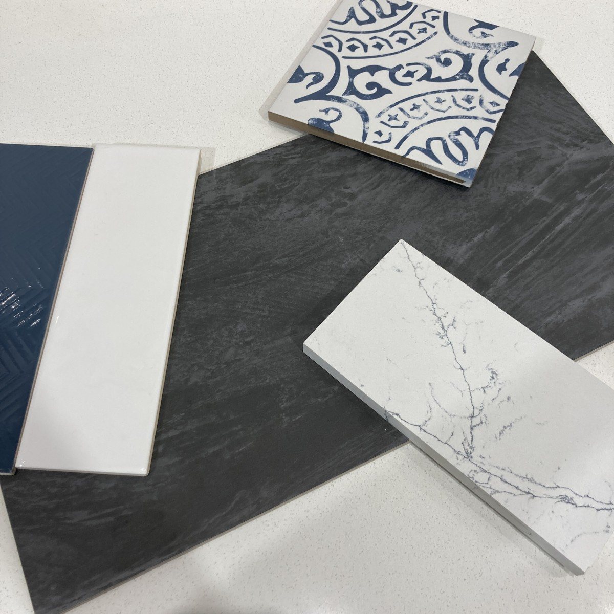 A mix of blue, white, and black ceramic and porcelain tiles, and quartz.